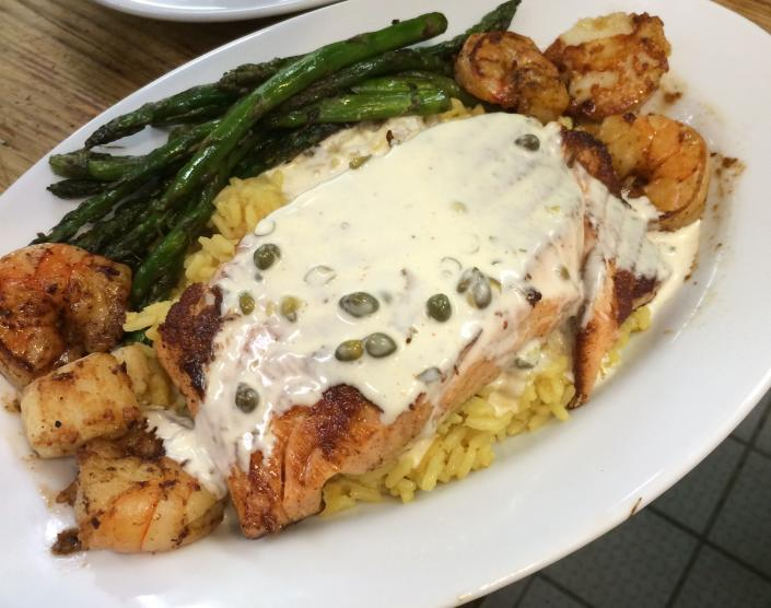 [Image: Grilled salmon with shrimp and scallops on bed of yellow rice with lemon butter caper sauce.  ]